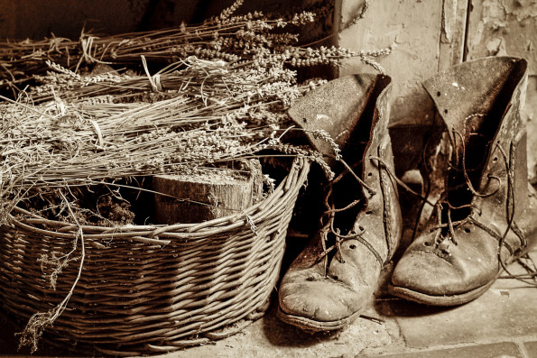 a pair of old boots next to a basket of lavender