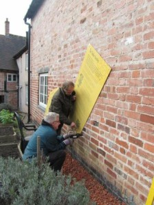 Two men attach a panel to a wall.