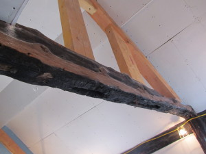 a blackened beam shows signs of fire damage