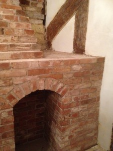 brick fireplace overlaps medieval timbers
