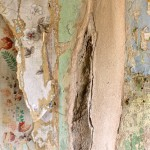 Peeling layers of patterned wallpaper.
