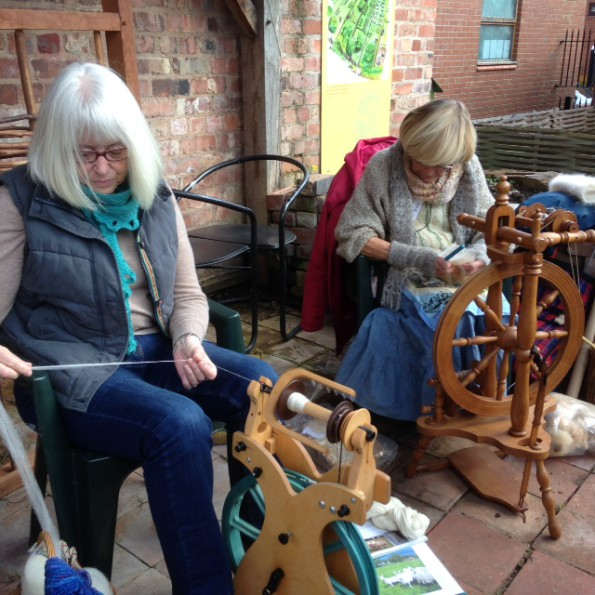 Two women demonstate spinning wheels