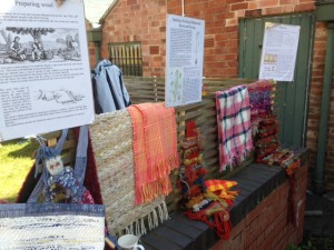 samples of woven fabrics are displayed in a garden