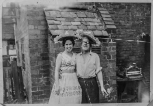 A young woman in a wedding dress stands next to her father