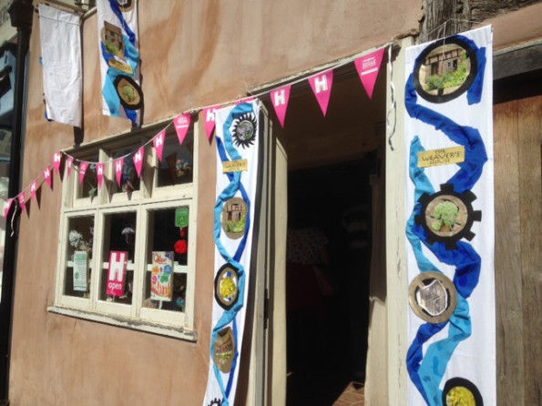 Pink bunting strung along the front of a small medieval building, long blue and white banners