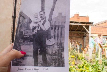 An old photo of a man and a baby in a back garden is held up against the same background today.
