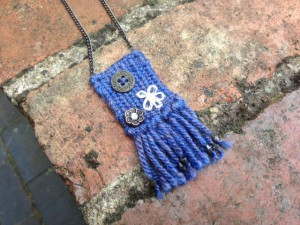 blue woven pendant with button and embroidery detail