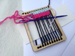 a small frame with thread running from top to bottom
