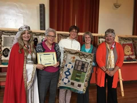 A woman dressed in medieval clothes and a group of women hold a certificate and a woven panel depicting the Weavers House