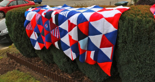 A red white and blue blanket made of knitted triangles