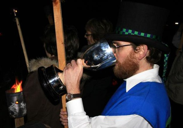 A man in morris costume drinking from a very big goblet