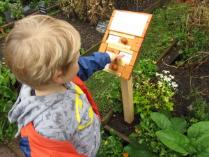 A young boy points to a sign in the garden