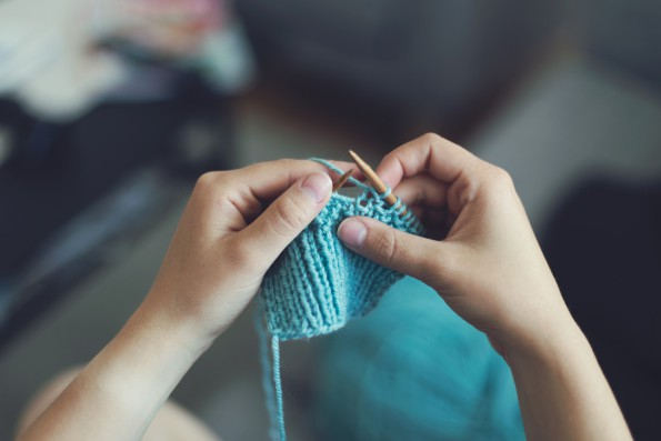 hands holding blue knitting and needles
