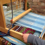 Cloth being woven on a small loom
