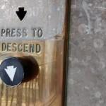 press to descend brass lift button