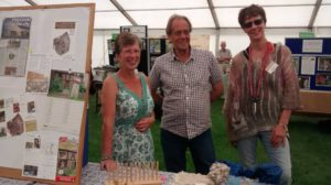 three people at a stall in a marquee tent