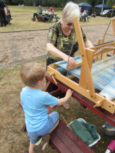 a child watches a loom demonstration