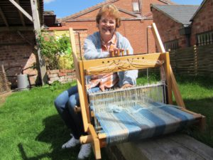 a woman in a sunny garden with a loom with blue threads