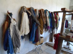 Hanks of wool hang on the wall, blue, brown, cream, beige