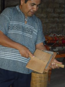 A man with two flat 'carding' brushes