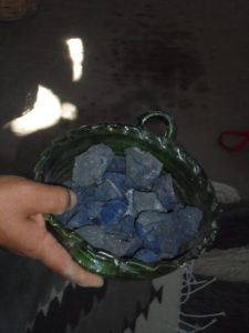 A small basket with bluish stones