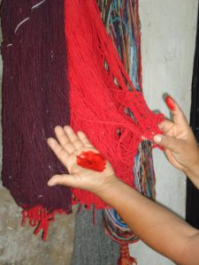 Two hanks of wool, one bright red and one maroon