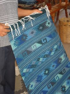A carpet with traditional Mexican patterning included diamonds and curls, in blue tones