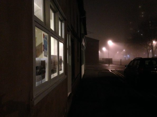 a small window cast light onto a misty street
