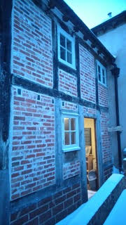 Weaver's House - a lit doorway onto a snowy garden