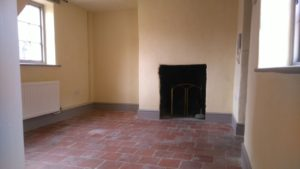 Interior of flat, tiled floor, black fireplace
