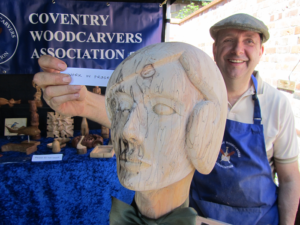 large carved head with label 'work in progress'