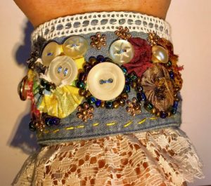 A fabric bracelet adorned with ribbon, buttons and beads