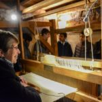 A group of teenagers are shown the large replica loom