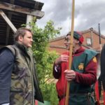 A visitor chats to a red and green clothed reenactor archer