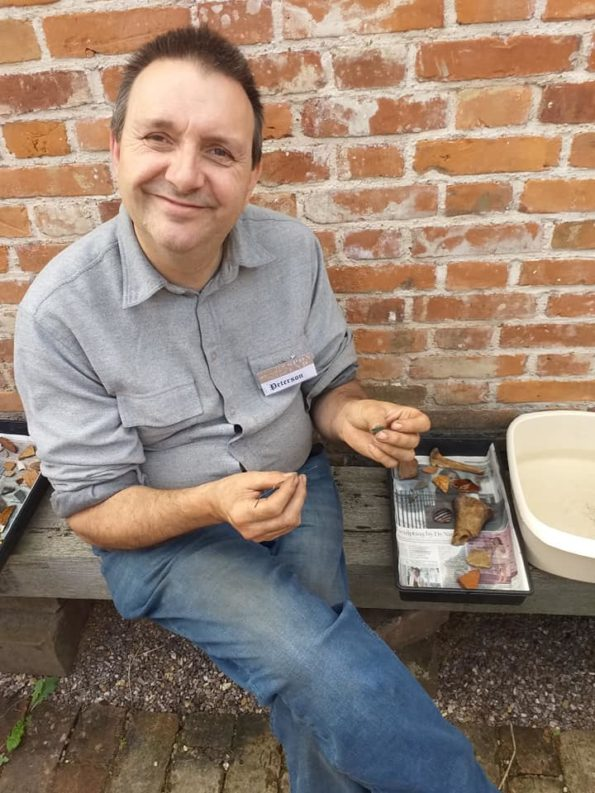 A man with a tray of items that have just been dug up