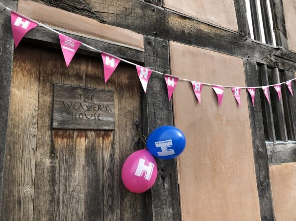 bright blue and pink balloons and bunting outside the medieval building