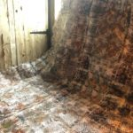 woven textile art in reds and browns covers the floor and wall of the house