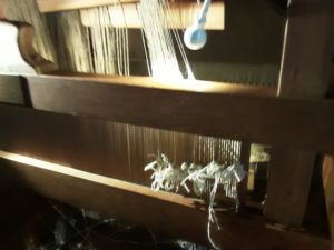 working on the loom illuminated by electric bulb shining on the threads