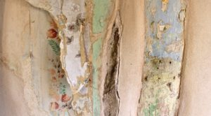 peeling layers of wallpaper - floral, plain, blues and greens