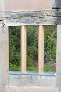 the wooden bars of a window frame the garden full of plants