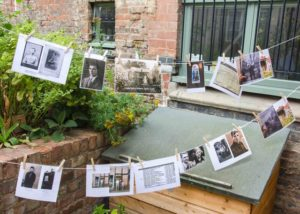 photos are strung on ribbon like bunting, across the garden