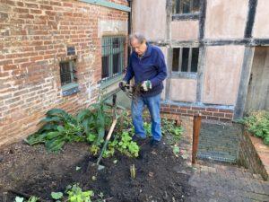 A man digs over a garden bed
