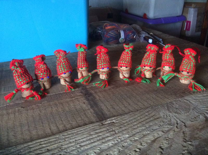A row of tiny Christmas elves with red hats