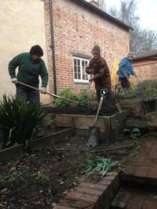 People dressed warmly raking and digging