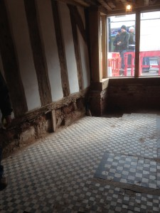 Chequered black and white floor tiles and medieval timbered wall
