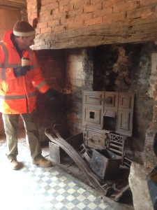 A man in hi-vis jacket points to a rusty oven