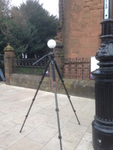 A tripod with a white ball on top