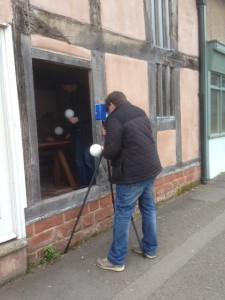A man using a tripod to laser scan a small medieval house.