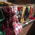 Samples of woven work are draped over a fence