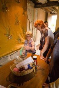 Two women study a flat woollen braid